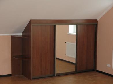 , необходимо становится задуматься какую именно мебель можно туда подобрать а, следовательно как ее расставить в комнате. Зачастую  на мансардном этаже располагается спальня. Но удобного спального гарнитура для мансарды в магазине найти не удастся, значит необходимо изготавливать мебель для мансарды на заказ. Мебель для мансарды достаточно сложно выбрать, потому то угол наклона крыши у каждого дома свой индивидуальный, разная высота потолков, геометрия помещения.  В итоге производители не могут предложить стандартного решения возникшей проблемы. Обычно,  к скошенной крышей стене ставится кровать, к противоположной стене — шкаф. Но стоит отметить, что Данный вариант не совсем удобен, так как при такой расстановке, нельзя полностью комфортно чувствовать себя на кровати – риск удариться головой о крышу достаточно велик. Но есть решение этой проблемы:  если выбрать встроенную мебель, из этого положения можно выйти, получив при этом функциональный и стильный вариант обстановки, не предоставляющий неудобств.